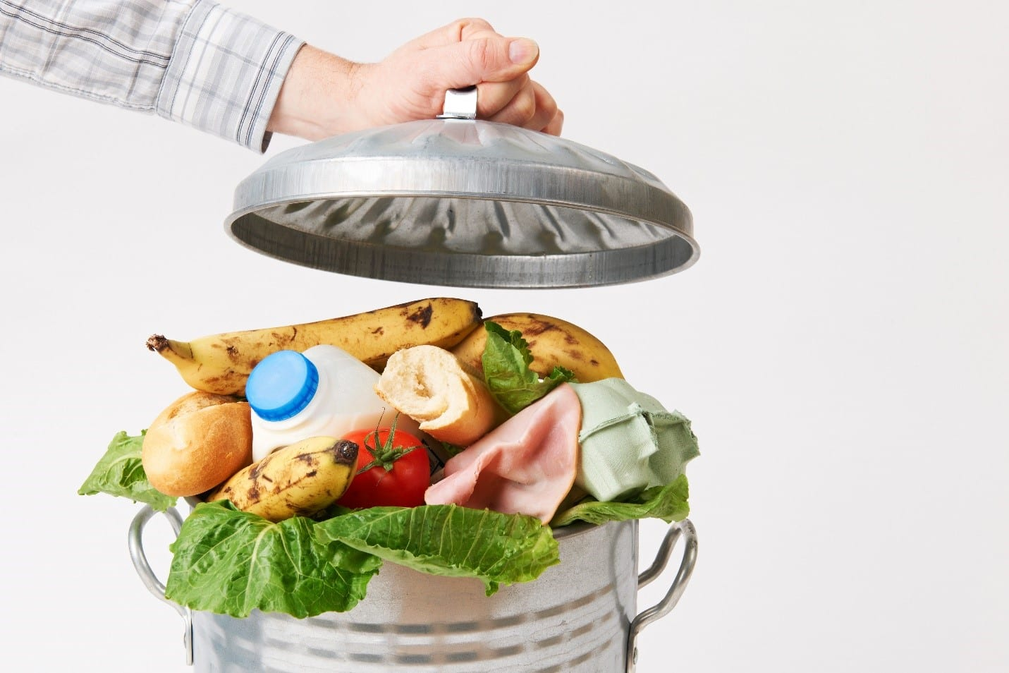 A trashcan full of still edible food with a man holding open the lid